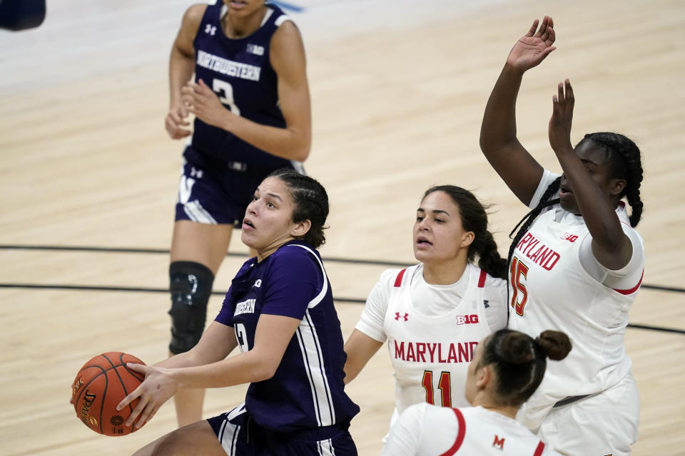 Northwestern's Veronica Burton (12) put up a shot ahead of Maryland's Katie Benzan (11) and Ashley Owusu (15) during the second half of an NCAA college basketball semifinal game at the Big Ten Conference tournament, Friday, March 12, 2021, in Indianapolis. (AP Photo/Darron Cummings)