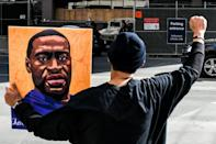 A demonstrator holds a portrait of George Floyd outside the Minneapolis courthouse where the trial of the police officer accused of his death is taking place
