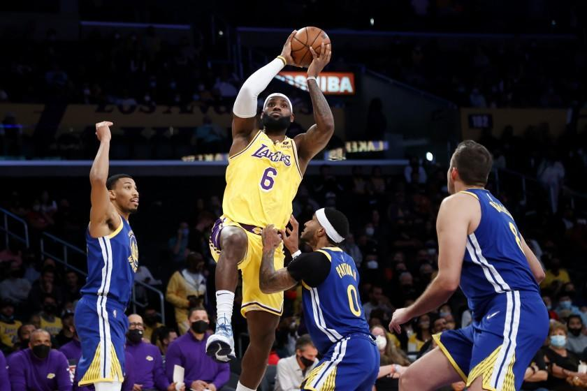 Los Angeles Lakers forward LeBron James shoots over Golden State Warriors guard Gary Payton II, second from right, during the first half of a preseason NBA basketball game in Los Angeles, Tuesday, Oct. 12, 2021. (AP Photo/Ringo H.W. Chiu)