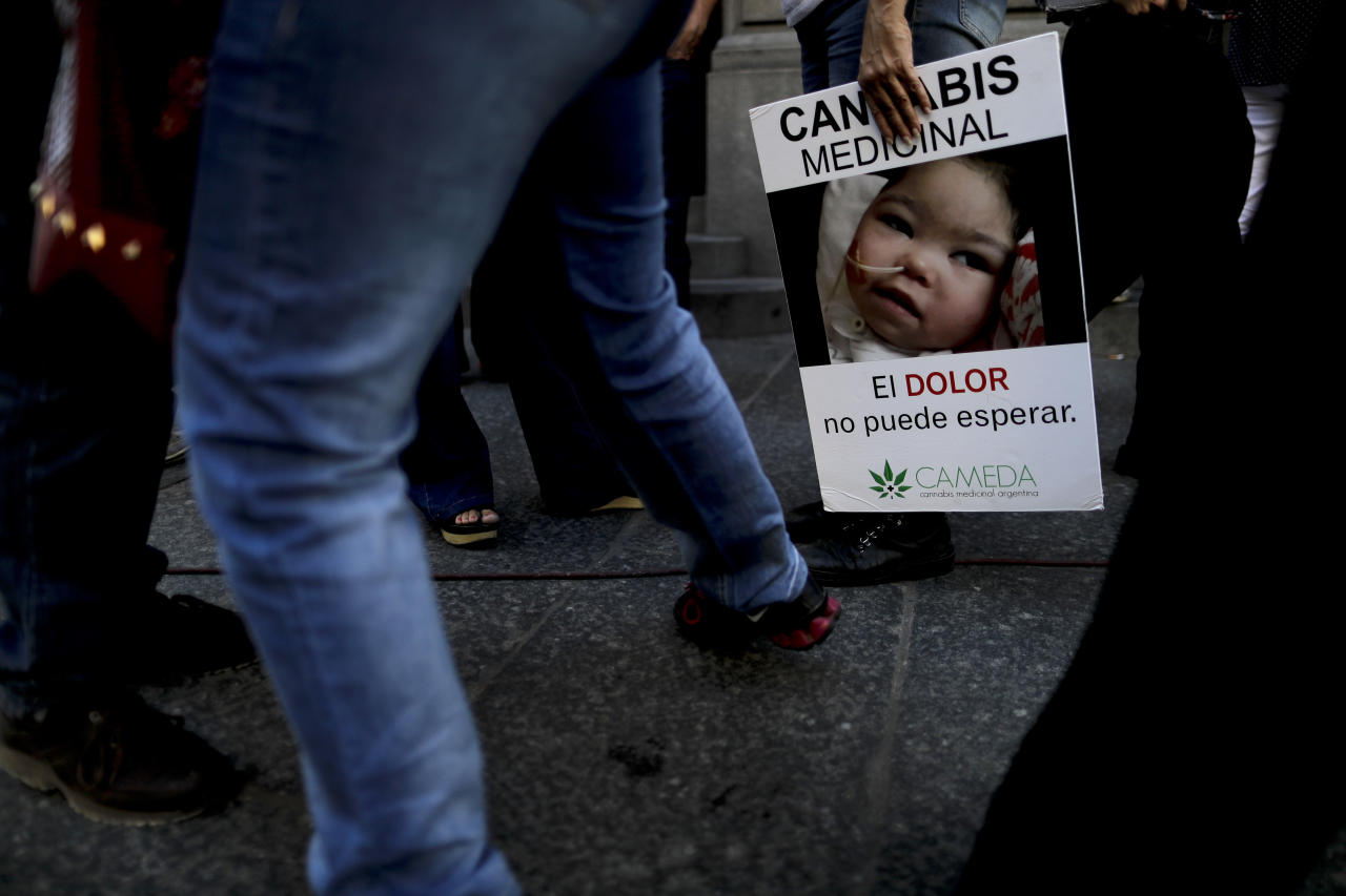 """A woman holds a banner with a message that reads in Spanish: """"Medicinal Cannabis, the pain can not wait"""", as she waits outside the Senate in Buenos Aires, Argentina, Wednesday, March 29, 2017. The Senate is expected to vote into law the medicinal use of marijuana on Wednesday. (AP Photo/Natacha Pisarenko)"""