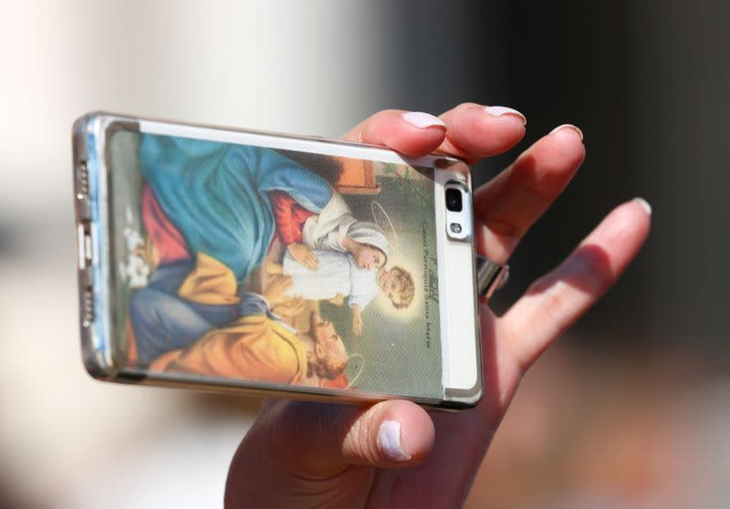 FILE PHOTO: A worshipper uses a phone with a cover depicting Holy Family as Pope Francis arrives to lead the Wednesday general audience in Saint Peter's square at the Vatican