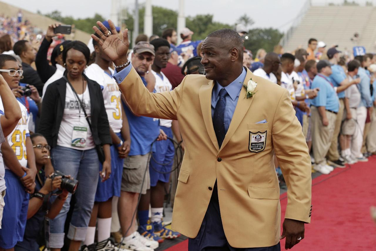 Hall of Fame inductee Derrick Brooks waves to fans as he is introduced during the Pro Football Hall of Fame enshrinement ceremony Saturday, Aug. 2, 2014, in Canton, Ohio. (AP Photo/Tony Dejak)