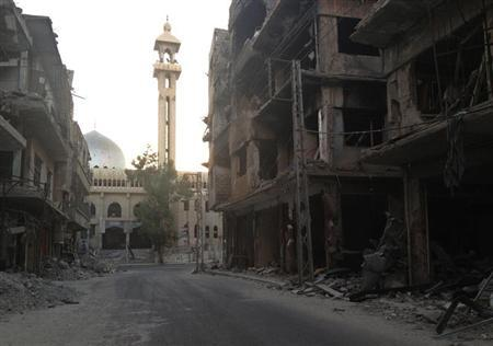 A general view shows damaged buildings along a deserted street in the Damascus suburb of Zamalka