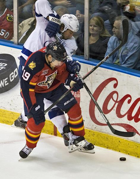 Florida Panthers forward Scottie Upshall (19) battles Tampa Bay Lightning's Pierre-Cedric Labrie during the first period of an NHL preseason hockey game Thursday, Sept. 26, 2013, in Estero, Fla. (AP Photo/Steve Nesius)