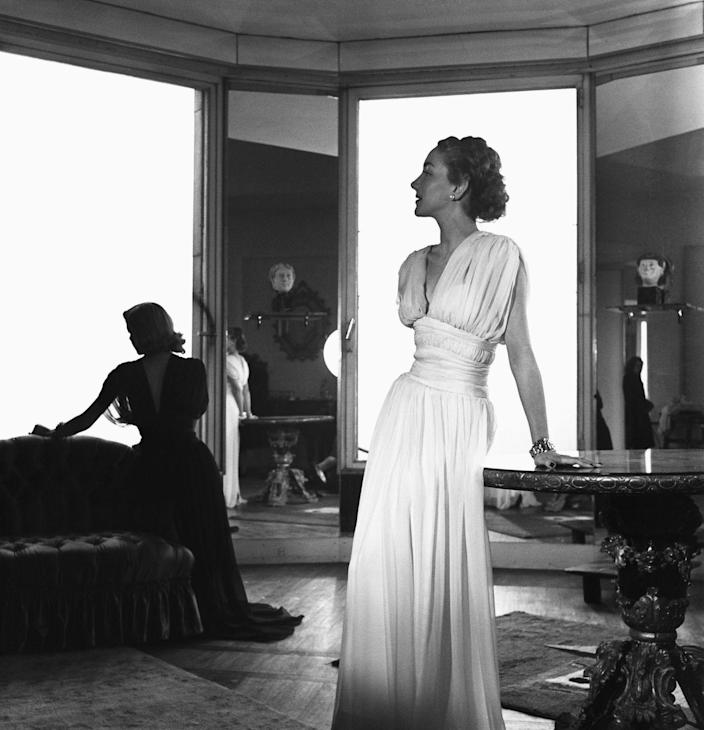 <p>One model wears a sheer white Molyneux dress, while another reclines in the shadows in a black Lanvin gown. </p>