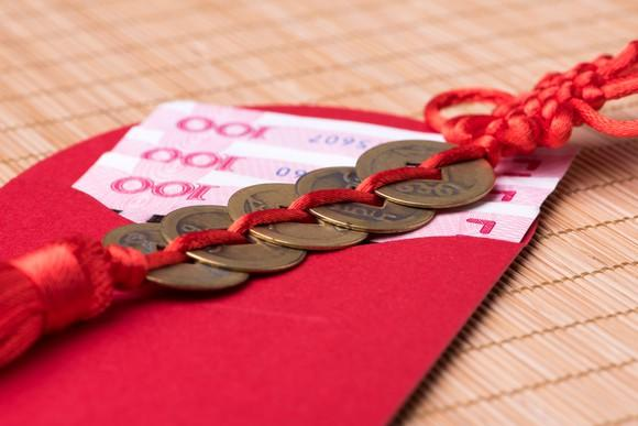 A red envelope filled with Chinese paper money with coins tied with red yarn resting on top of it.