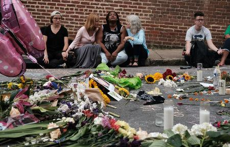 """Women sit by an impromptu memorial of flowers commemorating the victims at the scene of the car attack on a group of counter-protesters during the """"Unite the Right"""" rally as people continue to react to the weekend violence in Charlottesville, Virginia. REUTERS/Justin Ide"""