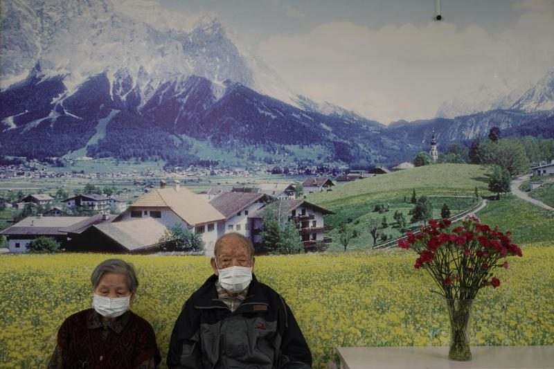 Elderly couple wearing protective face masks sit at a nursing home on Valentine's Day in Hong Kong, Friday, Feb. 14, 2020. China on Friday reported another sharp rise in the number of people infected with a new virus, as the death toll neared 1,400. (AP Photo/Kin Cheung)