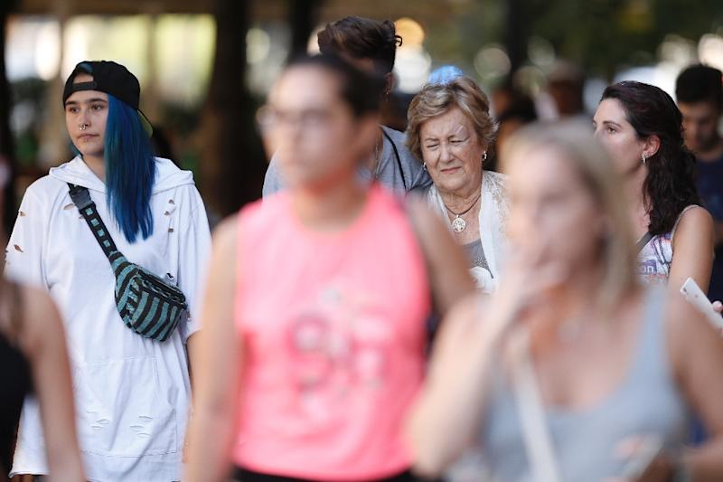 An elderly woman accompanied by young people reacts after a van ploughed into the crowd, killing two persons and injuring several others on the Rambla in Barcelona on August 17, 2017 (AFP Photo/Pau BARRENA CAPILLA)
