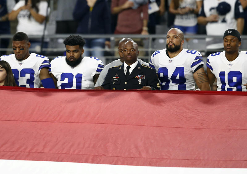 The Cowboys stand during the national anthem prior to Monday's game against the Cardinals. (AP)