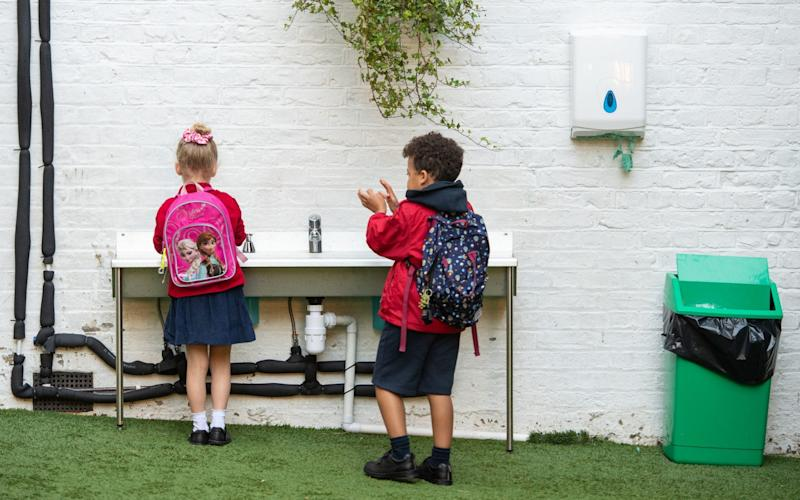 Pupils wash their hands as they arrive on the first day back to school at Charles Dickens Primary School in London
