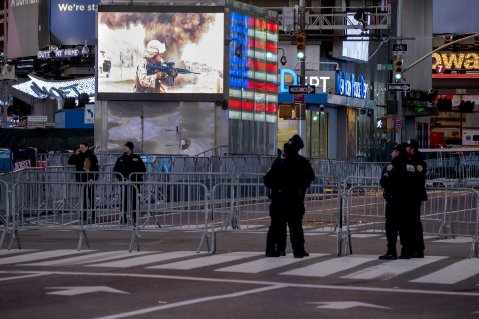Police officers stand along a mostly empty Seventh Avenue during what would normally be a Times Square packed with people in New York, late Thursday, Dec. 31, 2020, as celebrations have been truncated this New Year's Eve due to the ongoing pandemic. (AP Photo/Craig Ruttle)