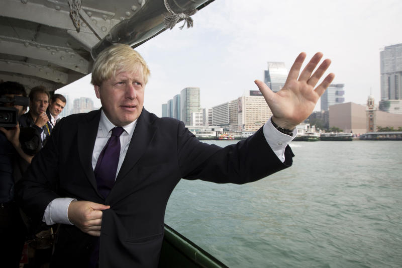 London Mayor Boris Johnson waves as he crosses Victoria Harbour on a Star Ferry during his visit in Hong Kong October 18, 2013. REUTERS/Tyrone Siu (CHINA - Tags: POLITICS)