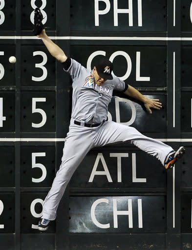 Miami Marlins left fielder Logan Morrison goes high but cannot make the catch, giving Houston Astros' Jordan Schafer a double, in the fifth inning of a baseball game on Wednesday, May 9, 2012, in Houston. (AP Photo/Pat Sullivan)