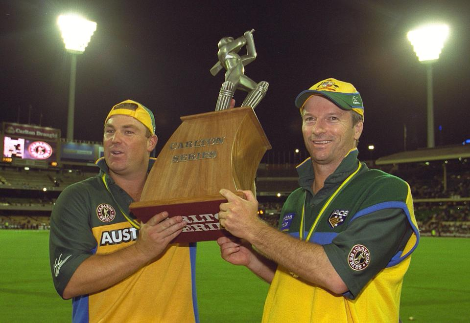 Shane Warne and Steve Waugh celebrate and lift the trophy.