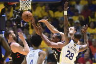 Toronto Raptors center Marc Gasol, left, and forward Kawhi Leonard (2) battle for a loose ball against Golden State Warriors forward Alfonzo McKinnie (28) and center Andrew Bogut, right rear, during the first half of Game 3 of basketball's NBA Finals, Wednesday, June 5, 2019, in Oakland, Calif. (Frank Gunn/The Canadian Press via AP)