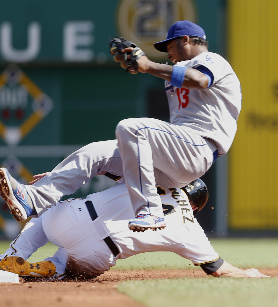 Los Angeles Dodgers shortstop Hanley Ramirez (13) tumbles over Pittsburgh Pirates' Gaby Sanchez after throwing to first to try and get out Russell Martin in the first inning of a baseball game on Saturday, June 15, 2013, in Pittsburgh. Sanchez was out on a fielder's choice but Martin was safe at first as Alex Presley scored from third on the play. (AP Photo/Keith Srakocic)
