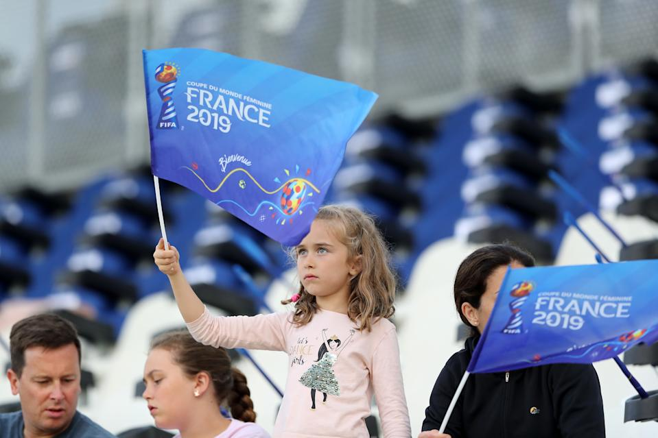 GRENOBLE, FRANCE - JUNE 15: A fan waves a FIFA Women's world cup flag prior to the 2019 FIFA Women's World Cup France group E match between Canada and New Zealand at Stade des Alpes on June 15, 2019 in Grenoble, France. (Photo by Elsa/Getty Images)