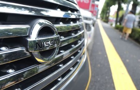 Pedestrian walks past Nissan Motor cars at the company's dealership in Tokyo