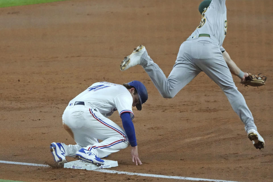 Texas Rangers' Eli White slides safely into third base past Oakland Athletics third baseman Matt Chapman as he advances on a wild pitch in the second inning of a baseball game Thursday, June 24, 2021, in Arlington, Texas. (AP Photo/Louis DeLuca)