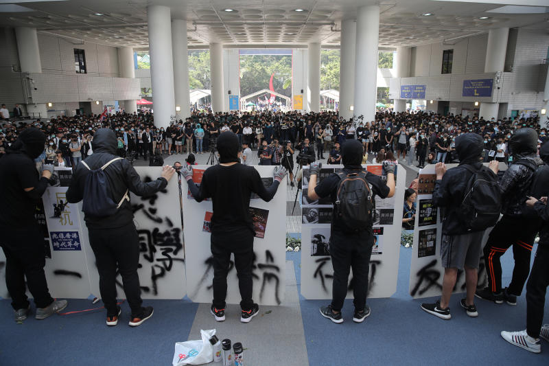 Protesters disrupt a graduation ceremony at the University of Science and Technology in Hong Kong on Friday, Nov. 8, 2019. The ceremony was cut short, and black-clad masked students turned the stage into a memorial for Chow Tsz-Lok who fell off a parking garage after police fired tear gas during clashes with anti-government protesters and died Friday. (AP Photo/Kin Cheung)