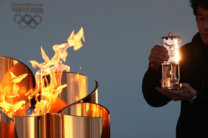 IWAKI JAPAN- MARCH 25 A staff preserves the Olympic flame to the lantern during the 'Flame of Recovery' special exhibition at Aquamarine Park a day after the postponement of the Tokyo 2020 Olympic and Paralympic Games announced due to the cor