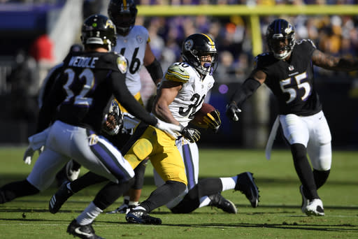 Pittsburgh Steelers running back James Conner, center, rushes the ball past Baltimore Ravens free safety Eric Weddle (32) and outside linebacker Terrell Suggs (55) in the first half of an NFL football game, Sunday, Nov. 4, 2018, in Baltimore. (AP Photo/Nick Wass)
