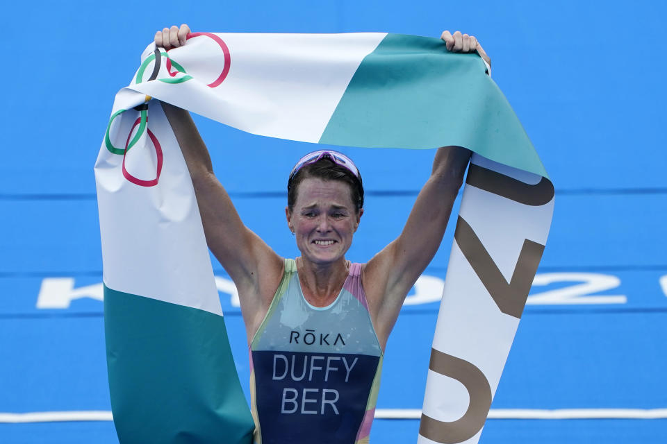 Flora Duffy of Bermuda celebrates after crossing the finish line to win the gold medal in the women's individual triathlon competition at the 2020 Summer Olympics, Tuesday, July 27, 2021, in Tokyo, Japan. (AP Photo/David Goldman)