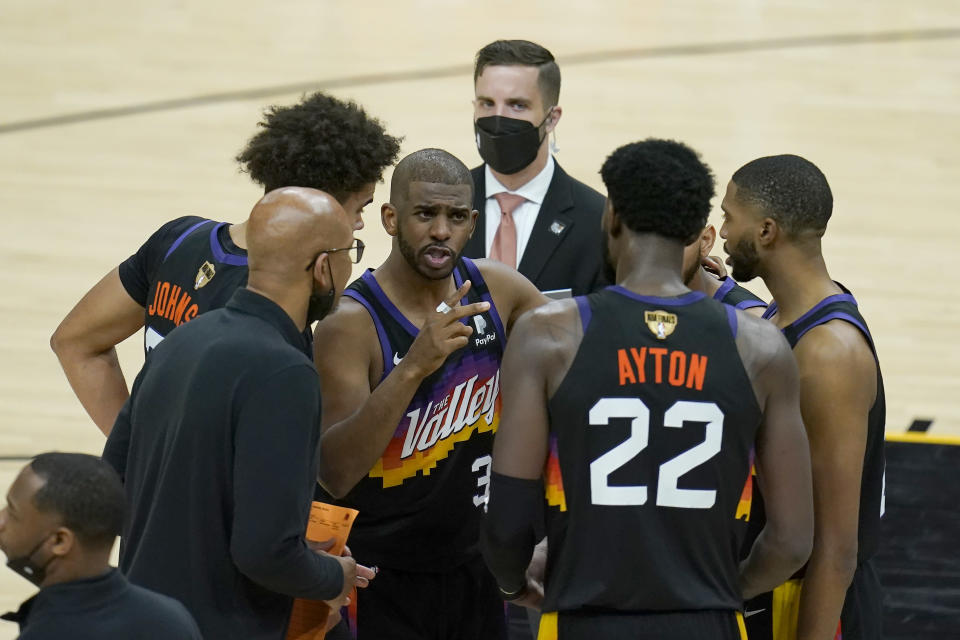 Phoenix Suns guard Chris Paul, middle, huddles with head coach Monty Williams, bottom left, center Deandre Ayton (22) and teammates during the second half of Game 5 of basketball's NBA Finals against the Milwaukee Bucks, Saturday, July 17, 2021, in Phoenix. (AP Photo/Ross D. Franklin)