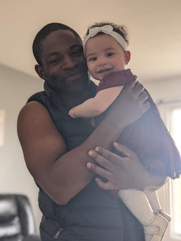 Franck Nana Ngassa holds his daughter, Makeba. Nana Ngassa's family is trying to send his body back to Cameroon after he was killed in a car crash in Arnprior, Ont., on May 13. (Submitted by Josie Pichette - image credit)