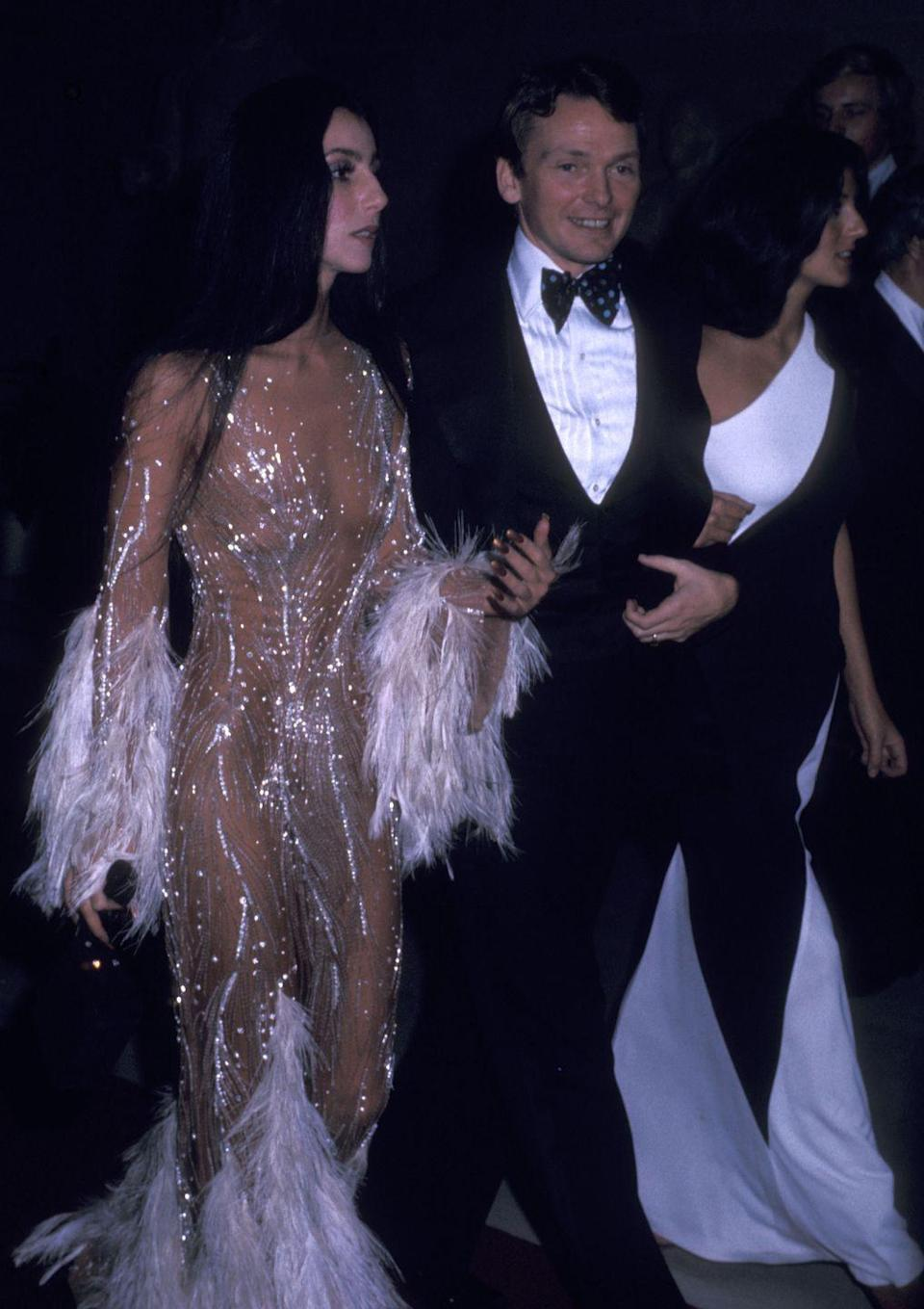 <p>Arriving to the 1974 Met Gala alongside Bob Mackie in the naked gown that inspired a red carpet trend decades later. The feathered and jewel-encrusted look was designed by Mackie. </p>