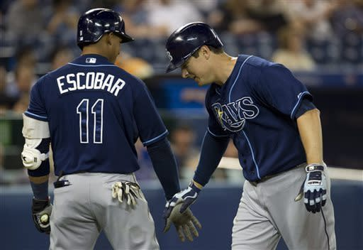 Tampa Bay Rays Kelly Johnson, right, is congratulated by teammate Yunel Escobar after hitting a home run off Toronto Blue Jays starting pitcher Ramon Ortiz during the second inning of a baseball in Toronto on Tuesday May 21, 2013. )AP Photo/The Canadian Press, Frank Gunn)