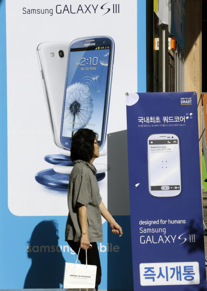 A woman walks near advertisements for Samsung's Galaxy S III smartphone in Seoul, South Korea, Thursday, Sept. 6, 2012. Samsung said global sales of its Galaxy S III smartphone have surpassed 20 million in a little more than three months. (AP Photo/Lee Jin-man)