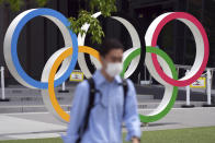A man wearing a protective mask to help curb the spread of the coronavirus walks near the Olympic Rings Wednesday, June 2, 2021, in Tokyo. (AP Photo/Eugene Hoshiko)