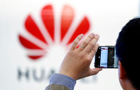 FILE PHOTO: A man takes a picture of a Huawei logo at the Huawei European Cybersecurity Center in Brussels, Belgium, May 21, 2019. REUTERS/Francois Lenoir/File Photo