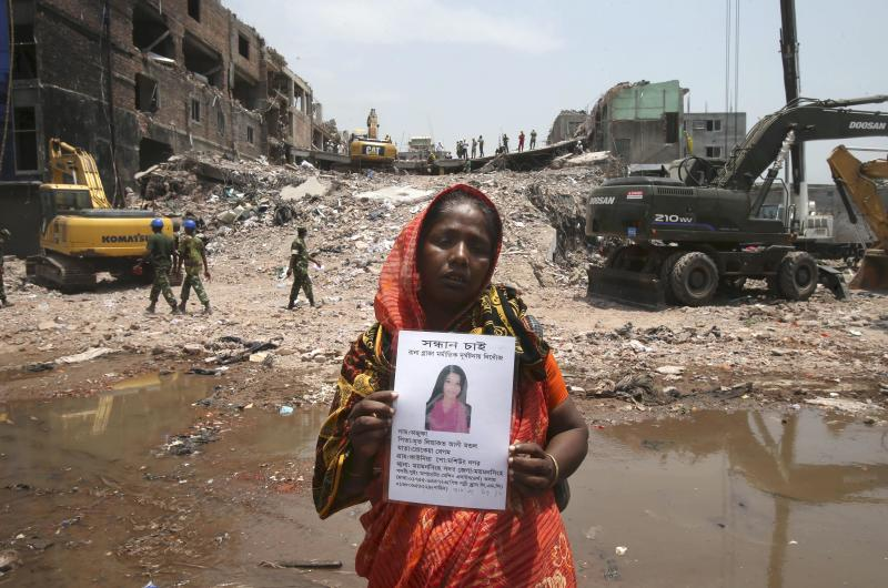 A woman lingers around the rubble holding a portrait of her missing daughter after a garment factory building collapsed last week in Savar, near Dhaka, Bangladesh, Friday, May 3, 2013 in Savar, near Dhaka, Bangladesh. Authorities suspended the mayor of the suburb of Savar, where the building was located, and arrested an engineer who called for the building's evacuation last week but was also accused of helping the owner add three illegal floors to the eight-story structure. (AP Photo/Wong Maye-E)