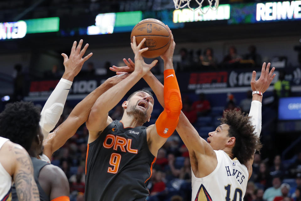 Orlando Magic center Nikola Vucevic (9) is fouled as he battles under the basket against New Orleans Pelicans center Jaxson Hayes (10) in the first half of an NBA basketball game in New Orleans, Sunday, Dec. 15, 2019. (AP Photo/Gerald Herbert)