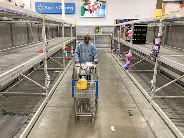 PHOTO: A shopper walks down an aisle that's normally stocked with toilet paper and other paper products at Walmart in Milwaukee, Wis., March 16, 2020. The impact of the coronavirus pandemic is causing area store's paper stock to become depleted. (Milwaukee Journal Sentinel via USA Today Network)