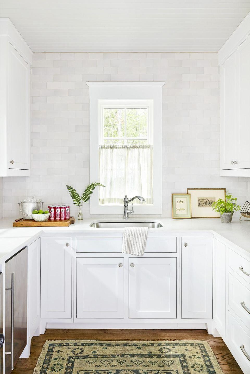 """<p>Using a Pearl Ash subway tile in this <a href=""""https://www.countryliving.com/home-design/house-tours/g4374/country-living-lake-house-of-the-year/"""" rel=""""nofollow noopener"""" target=""""_blank"""" data-ylk=""""slk:lake house kitchen and pantry"""" class=""""link rapid-noclick-resp"""">lake house kitchen and pantry</a> gives the white space added dimension in a subtle way.</p>"""