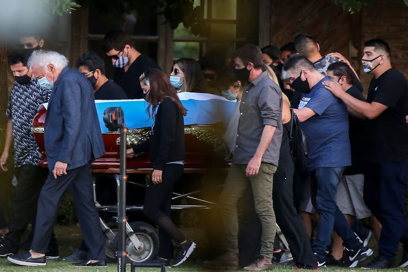 Friends and family carry the casket of soccer legend Diego Armando Maradona, at the cemetery in Buenos Aires