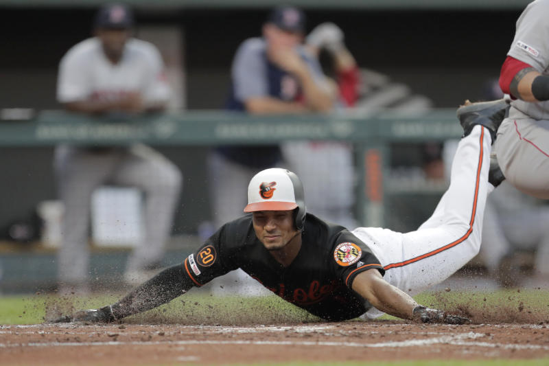 Baltimore Orioles' Richie Martin slides onto home while scoring against the Boston Red Sox in the second inning of a baseball game Friday, July 19, 2019, in Baltimore. Martin hit a triple off starting pitcher David Price and scored on a fielding error by right fielder J.D. Martinez. (AP Photo/Julio Cortez)