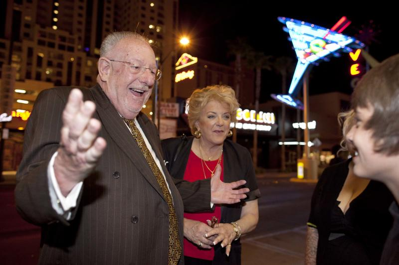 "In this April 1, 2011 photo, Las Vegas mayor Oscar Goodman, left, and his wife Carolyn Goodman greet pedestrians along Fremont Street while visiting businesses during First Friday, a social block party held the first Friday of every month, in Las Vegas. Since 1999, Las Vegas residents have been accustomed to finding the name Goodman on the election ballot for mayor. Tuesday will be no different. Except this time voters will see Carolyn Goodman's name replacing her husband's. Oscar Goodman, the self-proclaimed ""happiest mayor in the world,"" can't seek re-election after three terms and countless martinis and a field of 18 is vying in Tuesday's primary to succeed him.  (AP Photo/Julie Jacobson)"