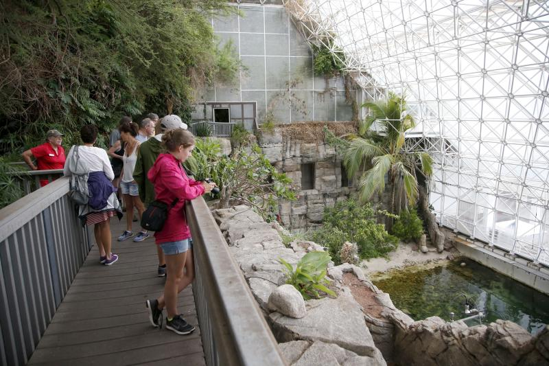 In this July 31, 2015 photo, tourists check out the Biosphere 2 Ocean, holding a million gallons of seawater, designed as an enclosed ecological system to research interactions within ecosystems, in Oracle, Ariz. University of Arizona officials say that 25 years after that New Age-style experiment in the Arizona desert, the glass-covered greenhouse thrives as a singular site for researchers from around the world studying everything from the effects of the ocean's acidification on coral to ways of ensuring food security. (AP Photo/Ross D. Franklin)