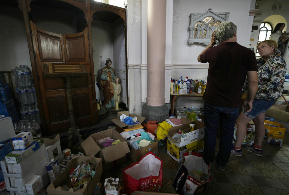 A volunteer speaks with a local resident at a local church which has been converted in a flood victims aide center in Trooz, Belgium, Tuesday, July 27, 2021. Uncontrollable water destroyed approximately half of the homes in the small village of Trooz, leaving tons of debris in its wake in one of the most violent natural disasters to hit Belgium in a century. (AP Photo/Virginia Mayo)