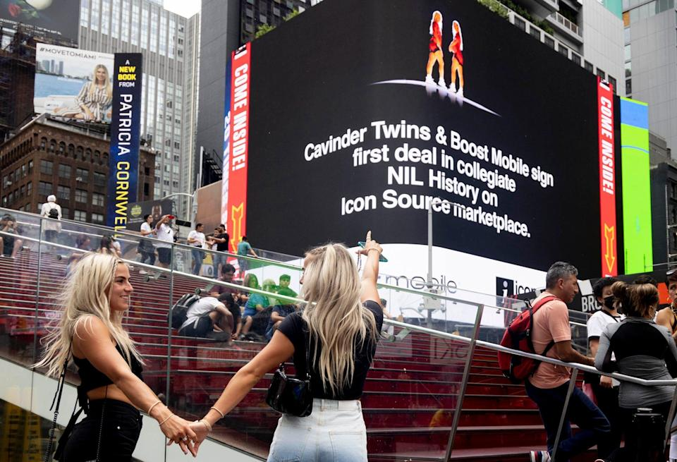 The Cavinder twins celebrate in Times Square as a billboard announces their deal with Boost Mobile on July 1, the first day collegiate athletes could cash in on their name, image and likeness.