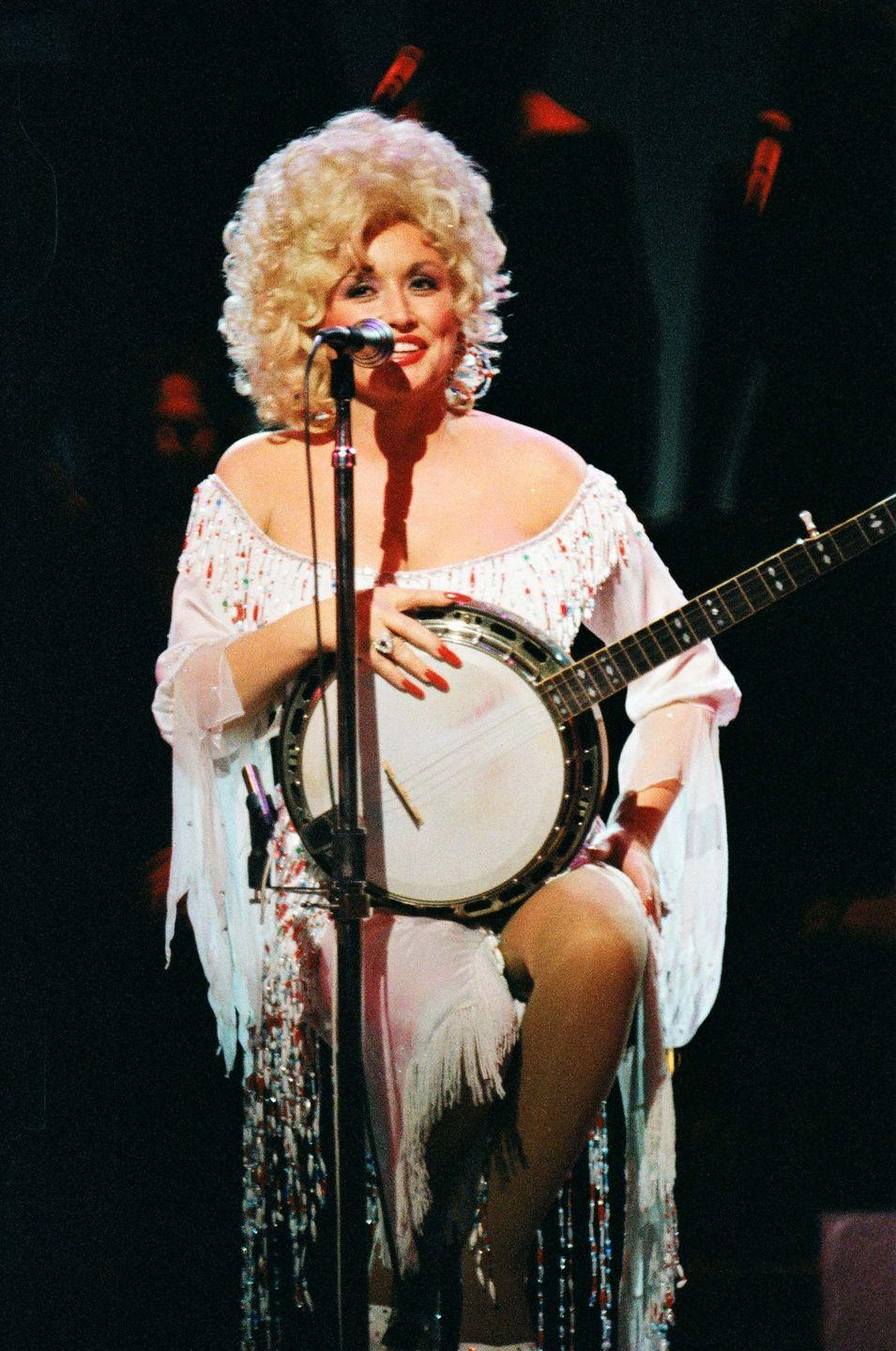 """<p>Parton plays at The Dominion Theatre in London all dressed up in colorful, beaded fringe. By this time in 1983, Parton had extended her fanbase worldwide after collaborations with singers like Olivia Newton-John, Emmylou Harris, and Linda Ronstadt. However, her fame was cemented after starring alongside Jane Fonda and Lily Tomlin in """"9 to 5.""""</p>"""