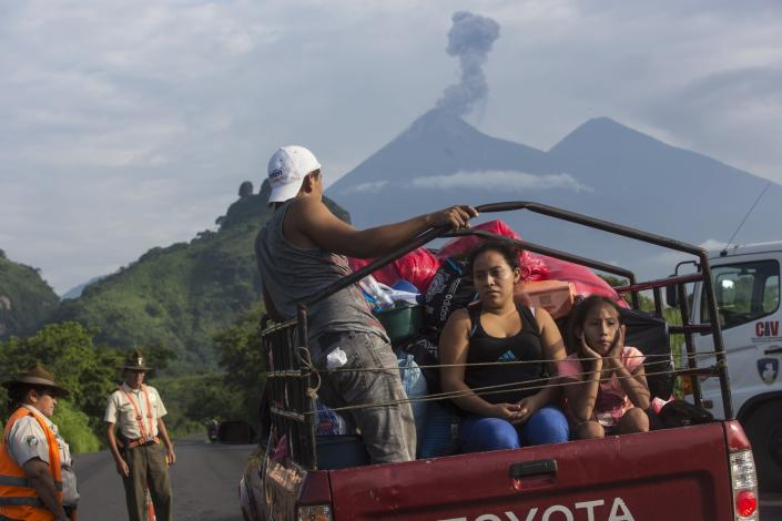 Villagers stop at a government checkpoint in Guatemala as the Volcan de Fuego expels gas near San Miguel Los Lotes on June 12, 2018. (Photo: Rodrigo Abd/AP)