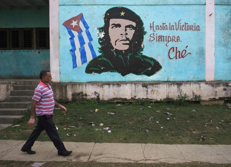 "A man walks past near an image of revolutionary hero Ernesto ""Che"" Guevara in Havana December 27, 2014.  Cuba's most prominent dissidents say they have been kept in the dark by U.S. officials over a list of 53 political prisoners who will be released from jail as part of a deal to end decades of hostility between the United States and Cuba. Picture taken December 27, 2014. REUTERS/Stringer (CUBA - Tags: POLITICS SOCIETY)"