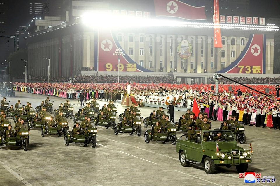 North Korean solders parading on vehicles.