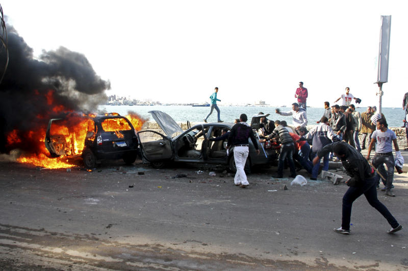 Cars burn during clashes between supporters and opponents of President Mohammed Morsi in Alexandria, Egypt, Friday, Dec. 14, 2012, a day before the referendum on the constitution.  Opposing sides in Egypt's political crisis were staging rival rallies on Friday, the final day before voting starts on a contentious draft constitution that has plunged the country into turmoil and deeply divided the nation.(AP Photo/Ahmed Ramadan)